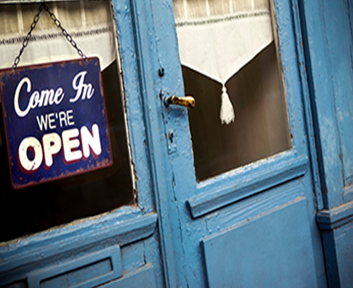 """Michael J Bell Law Office, Small business services, photo of window with """"come in we're open"""" sign."""