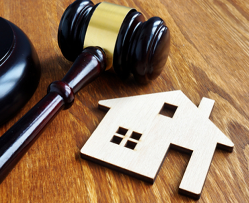 Real Estate photo of a cut out of a house and a law hammer